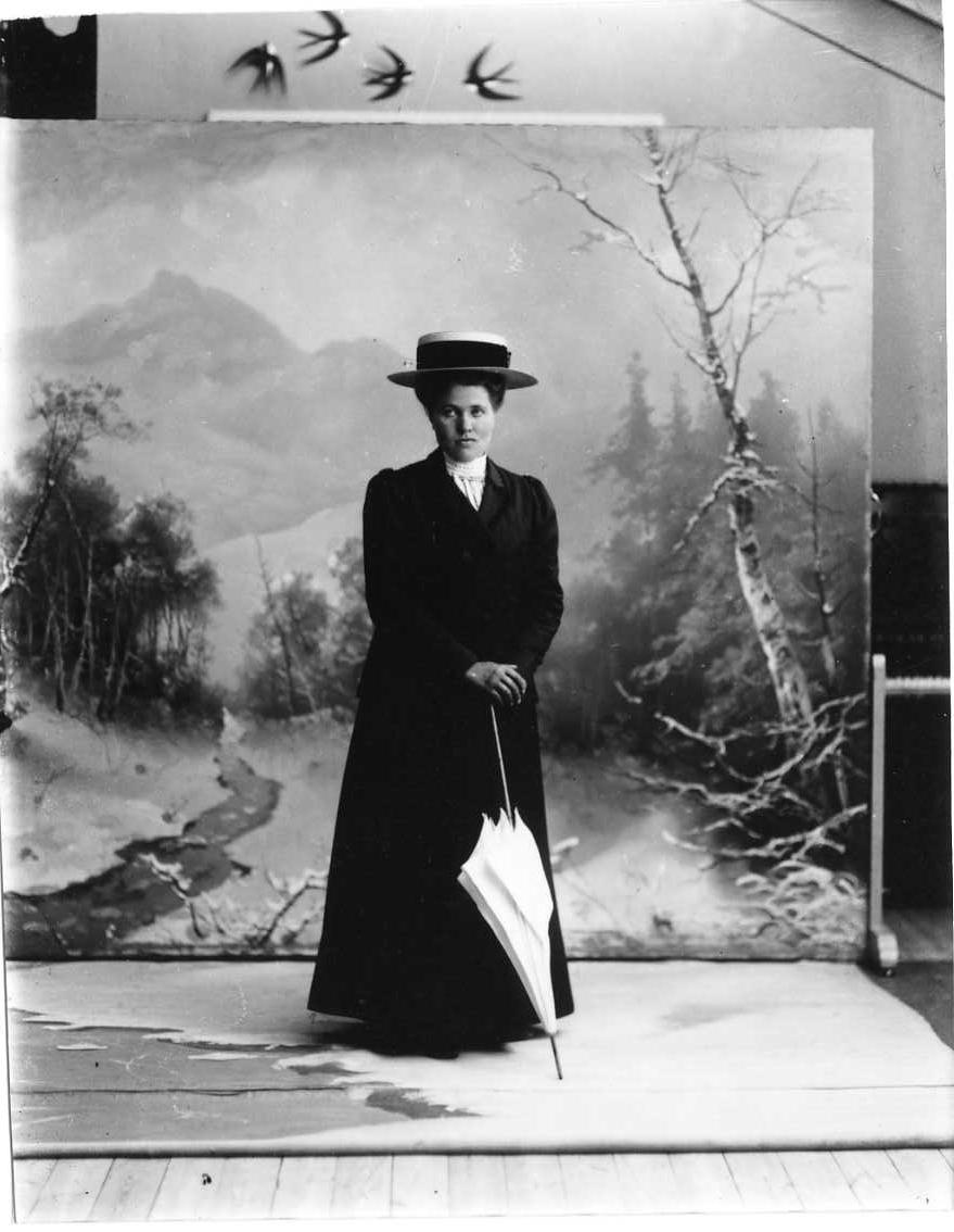Porträtt av Anna Johansson från Fallet i Gränna socken. Hon står med ytterkläder, hatt och parasoll framför en vinterfond.