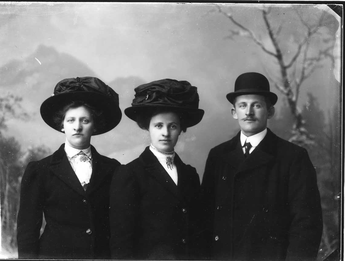 Gruppbild med syskonen Carlsson, från vänster: Elin, Jenny och Tedor. De står med ytterkläder och hatt framför en vinterfond.