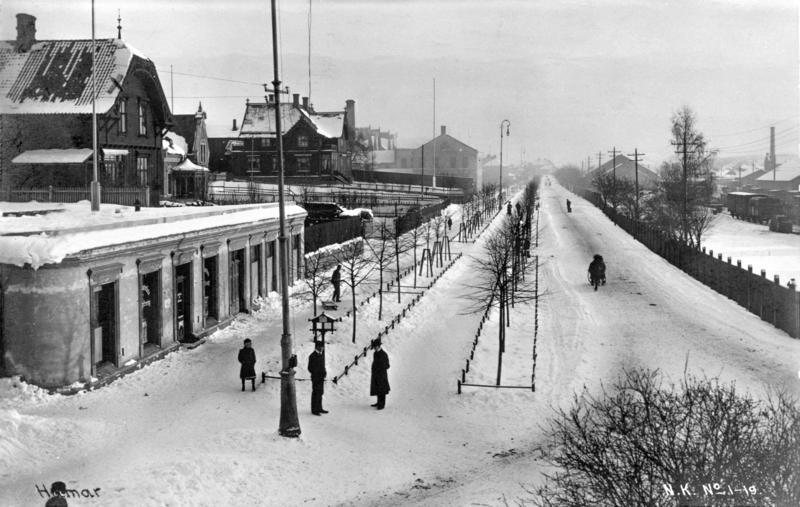 Svart-hvitt foto av snøhvit, rett gate som går rett innover i bildet. På høyre side skimtes et gammelt tog, det er noen menn i frakk og hatt som står i vegen, og på venstre side noen staselige trehus og et lavt murbygg med rundt hjørne. (Foto/Photo)