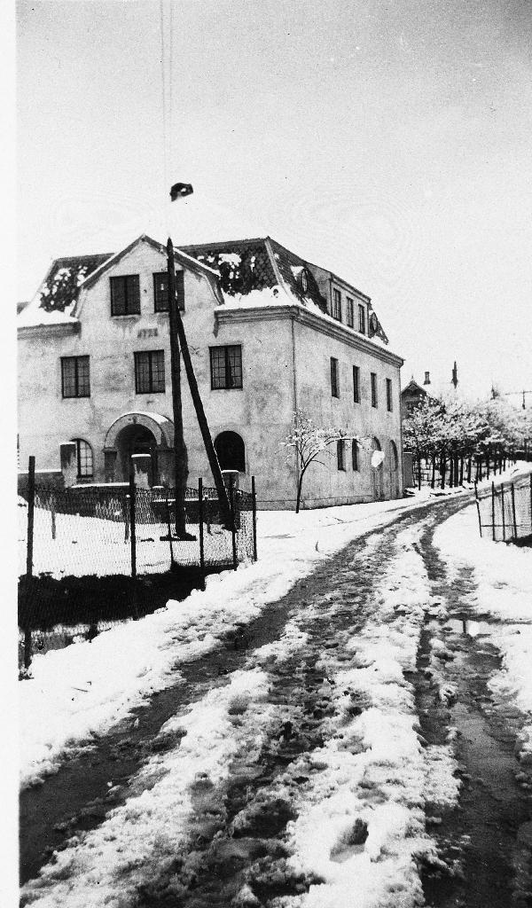 """""""Festiviteten"""", eigedomen til Bryne Vel fotografert 30. april 1927. Bygningen vart oppført i 1926. I andre høgda dreiv dei kino og salen vart og brukt til dansetilstelningar.  og festar av ulike slag. I første høgda heldt brannstasjonen til i mange år.  Under 2. verdskrig hadde Rogaland off. Landsgymnas klasserom i bygningen. Thv. Solberg driv nå (1990) elektrisk forretning her."""