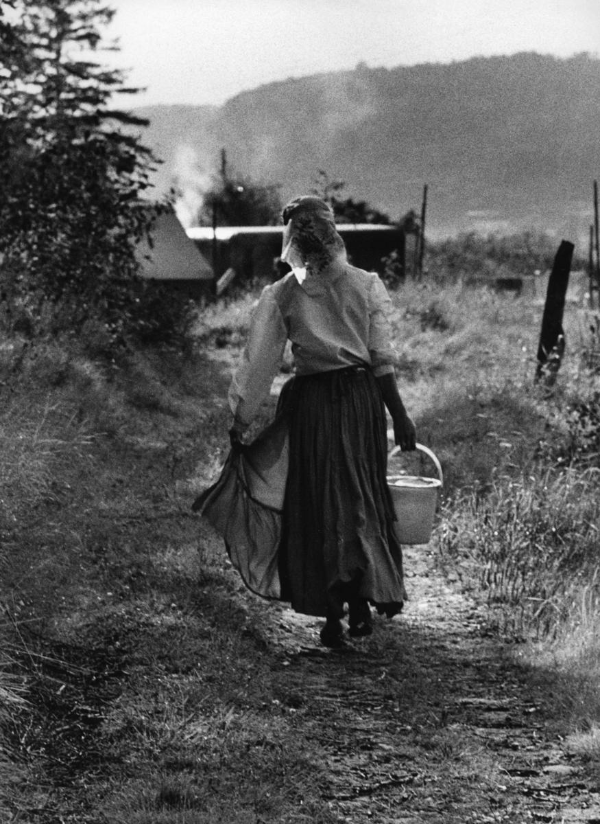 """En romsk kvinna går på en stig bärandes en hink med vatten. Bilden är troligen tagen i samband med inspelningen av TV-programmet """"Du svarte zigenare"""", ett program av Victor Lindgren. Programmet sändes första gången 1960-08-30.  I en återgiven intervju för en studie av Delegationen för romska frågor (2010) berättar en intervjuperson om hur det i hennes barndom ansågs bringa otur att gå med en tom hink genom lägret. Istället var man tvungen att med den tomma hinken gå bakom tältet och vagnarna för att hämta vatten."""