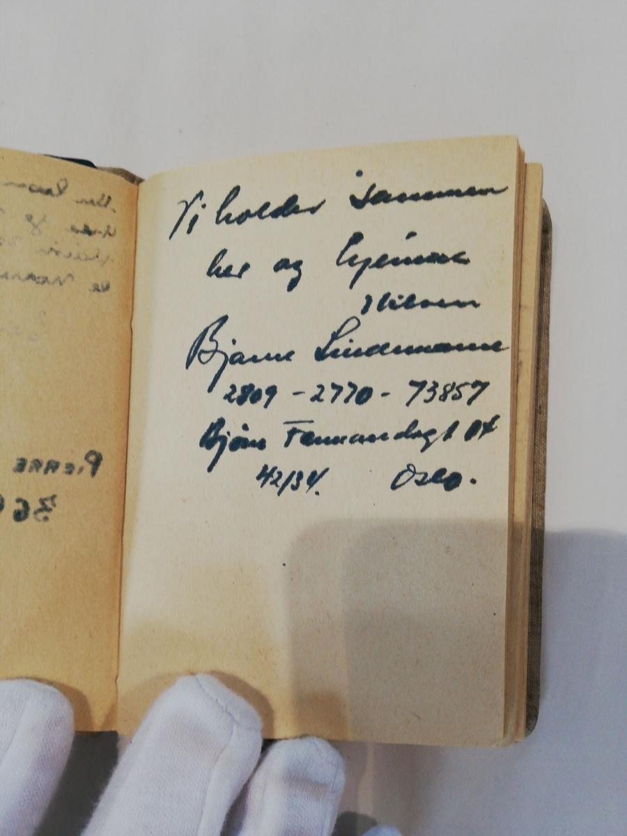 Notisbok inneholdende fangenummer og navn på i underkant av 160 personer. Noen personlige hilsener med navn og nummer.