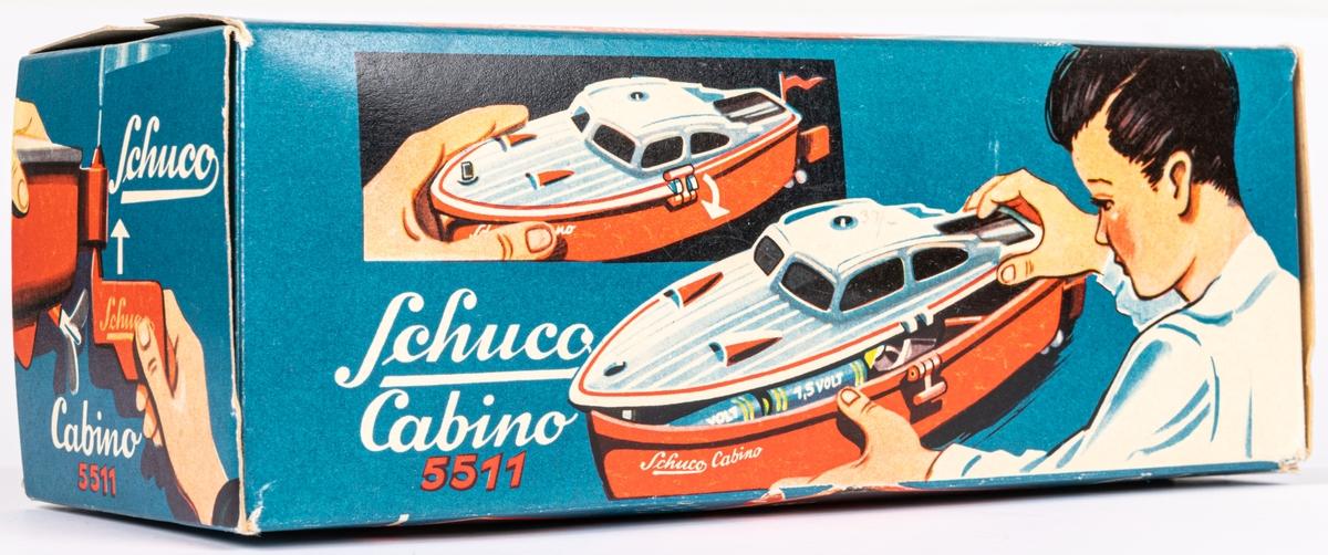 Leksaksbåt av gjuten hårdplast. Rött skrov och grått däckparti. Drivs med batteri. Ett batteri finns kvar. Båten ligger i orginalförpackning med bruksanvisning på engelska. Modell Cabino 5511. Tillverkad av Schuco i Tyskland.