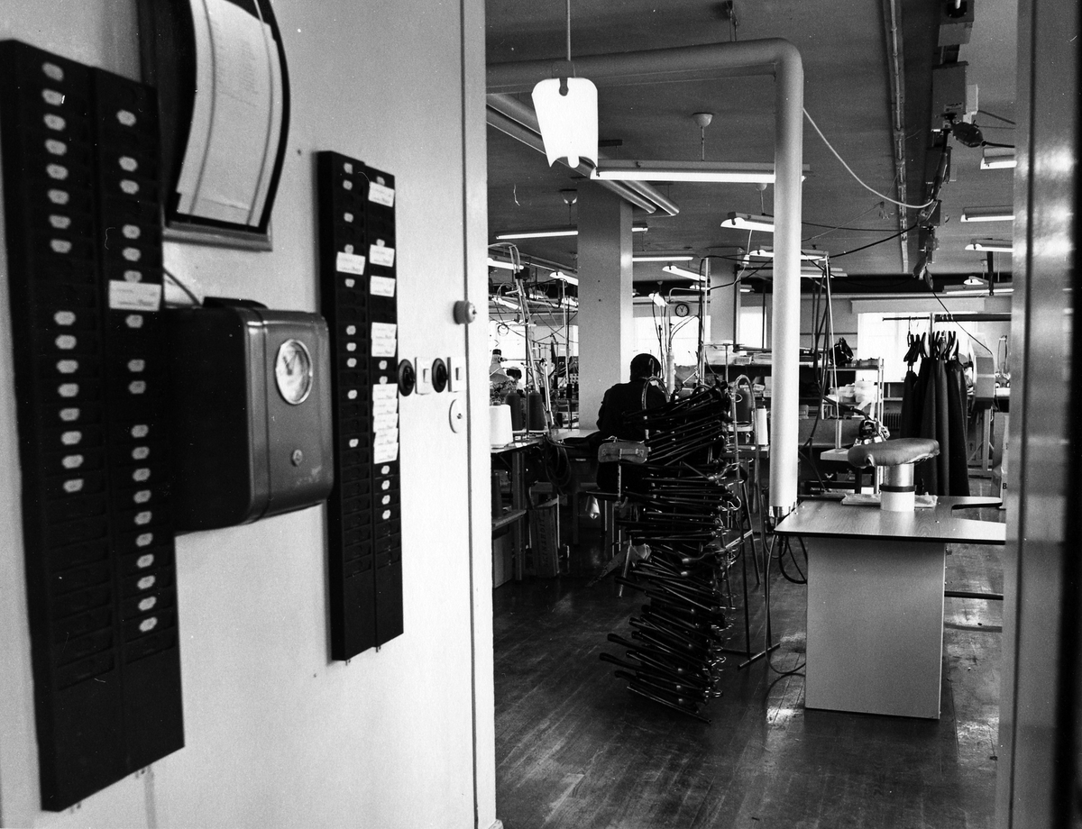 Drabant AB:s byxavdelning på tredje våningen sedd från entrédörren. En kvinna jobbar vid ett bord och till vänster i bild sitter en stämpelklocka.