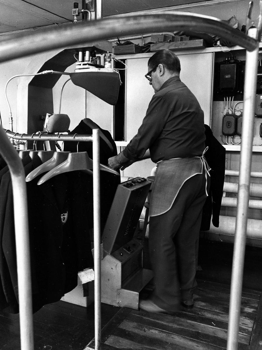 """En man jobbar med formade pressar för olika delar av kavajen. """"Pressen"""" eller avpressen, låg i samma rum som avsyningen. Drabant AB:s bottenvåning."""