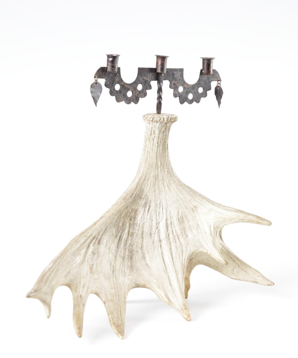 En tvåarmad ljusstake i genombrutet smide med tre ljuspipor, samt två hängande löv på vardera sidan. Smidet sitter monterat på ett 10-taggat älghorn som fot.