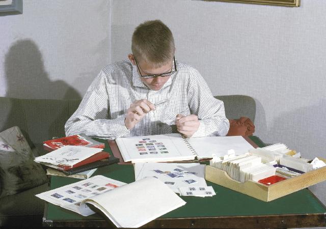 Seriebild M 14. Ung frimärkssamlare studerar frimärken med förstoringsglas. Han är omgiven av frimärksalbum och kataloger.