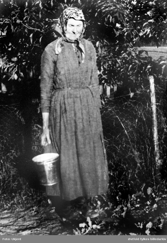 Mathea Kassem f. 1860 bærer vann, ved brønnen til gården Kassem i Skiptvet ca. 1923.