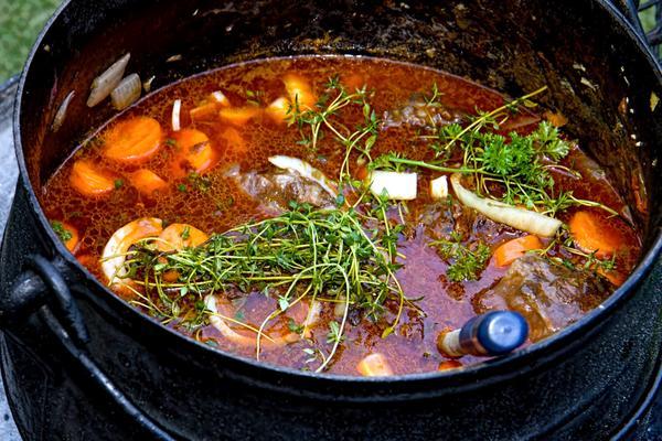 Smijernsgryte fylt med brunrødlig suppe med gulrotbiter, løk og grønne urtekvister.. Foto/Photo