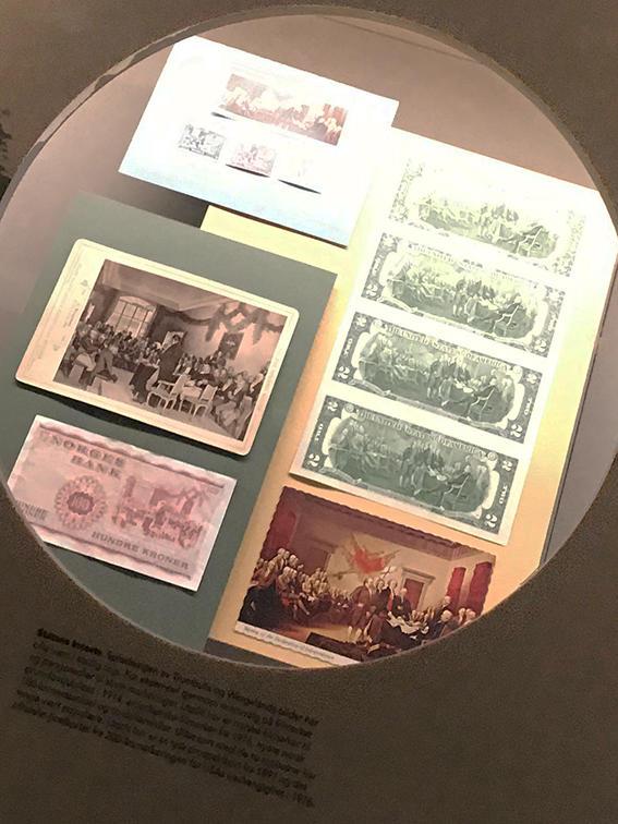 Foto av gjenstander i monter i utstillingen der de to maleriene er motiver på postkort, sedler og frimerker. (Foto/Photo)