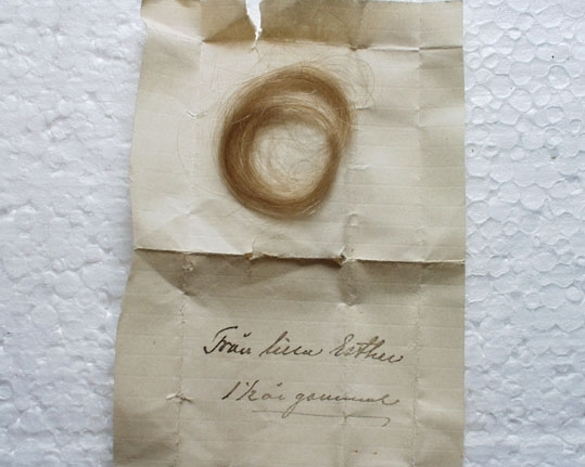 Anmärkningar: Schatull manikyretui av brunt läder, mönsterpressat och beslaget med metallnitar, rombisk pärlemoplatta i oval med röd sammet. Metall beslag runt öppningen. Invändigt klätt med lila moiré. Innehåller manikyrtillbehör. Format 15 x 6 x 5,5 cm.