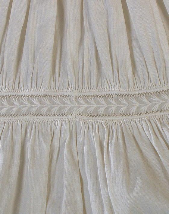 Vit klänning i tuskaftat bomull av ripskaraktär. Rund halsringning, knäppning fram, hyskor och hakar. Fram- och bakstyckena rynkade mot midjelinningen med stripade rynkor. Rynkad kjol med brett upplägg (39 cm). Infällda broderade band på livet och ärmarnas nederdel. Fårbogsärm med rynkad spetskantad volang isydd med passpoal. Avsmalnande snäv ärmnederdel med draperade partier mellan infällda broderade band prydda med klädda knappar i överkanten. Ärmen avslutas med manschetter av två broderade band. Knäpps med tre hyskor och hakar.