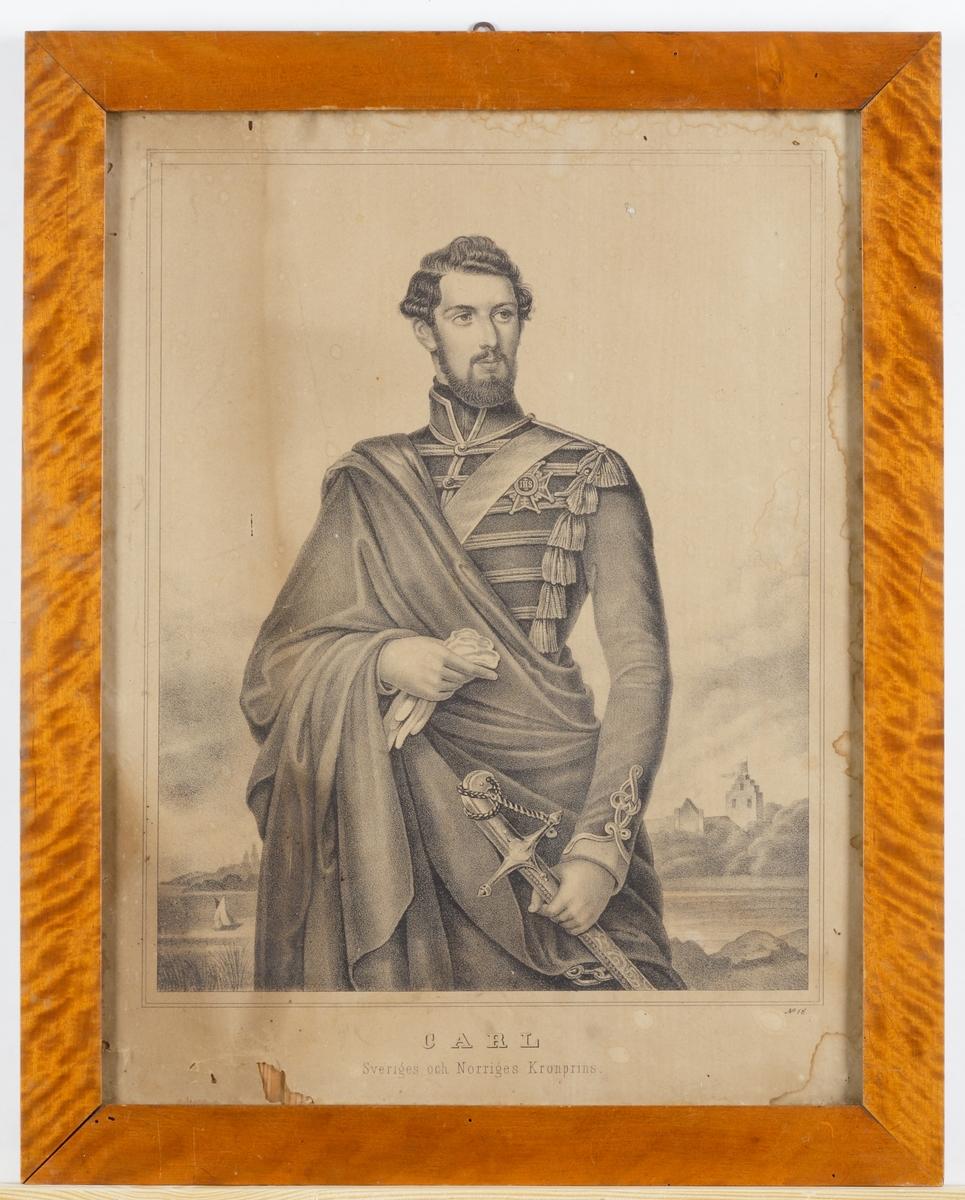 """Litografi föreställande Karl XV som kronprins. Knäbild, halv en face vänster, huvudet vridet åt höger. I bakgrunden landskap. Text: """"Carl Sveriges och Norriges Kronprins"""". """"No 16"""". Omgärdas av en björkram."""