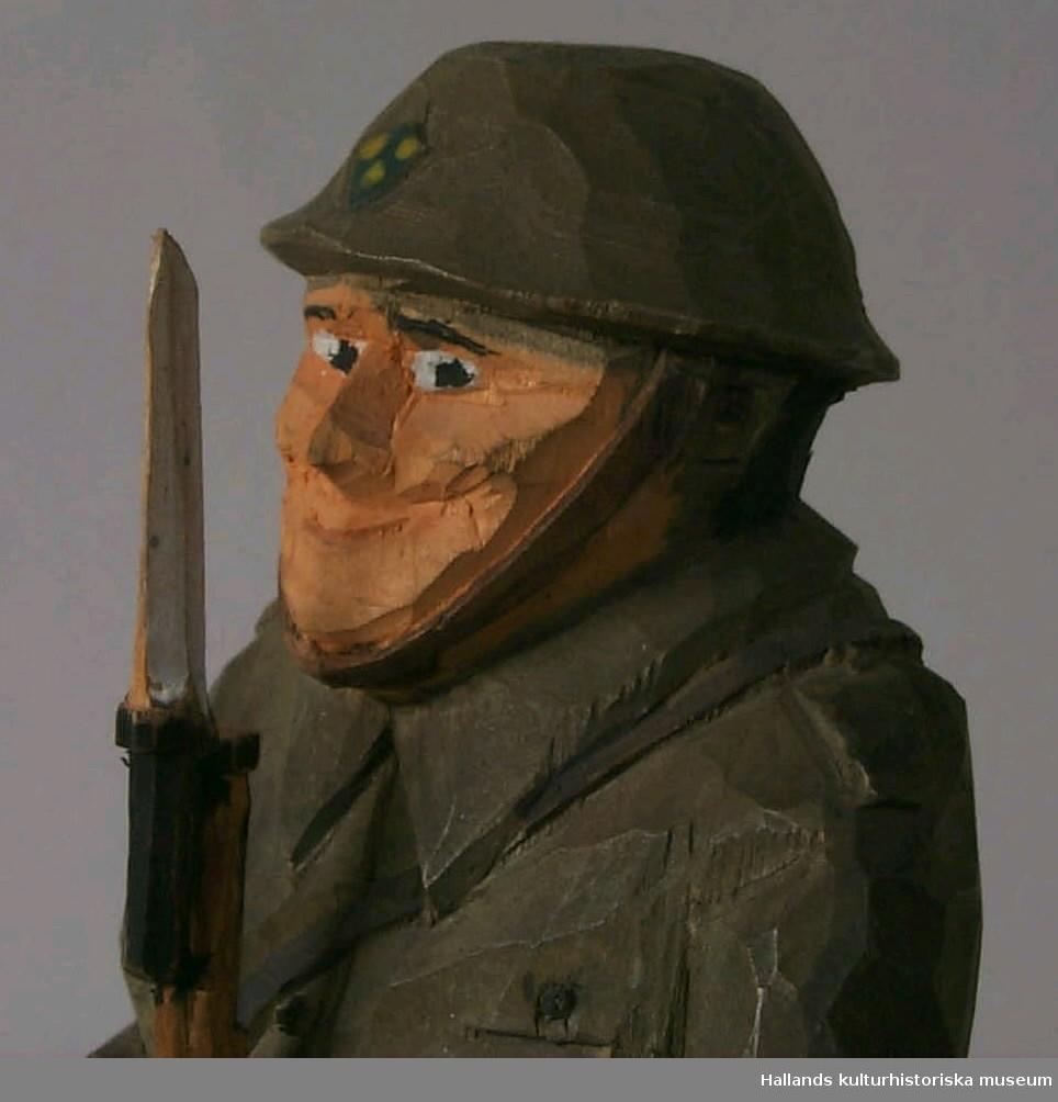 """Snidad mansfigur i trä. Föreställer svensk beredskapsman i uniform från andra världskriget, med gevär med bajonett. Målad i grågrönt, svart, beigt samt litet blått och gult. Glad. Står på Plywood platta. Märkning: """"Ivan Jonasson Ysby 1941"""", med bläck undertill."""