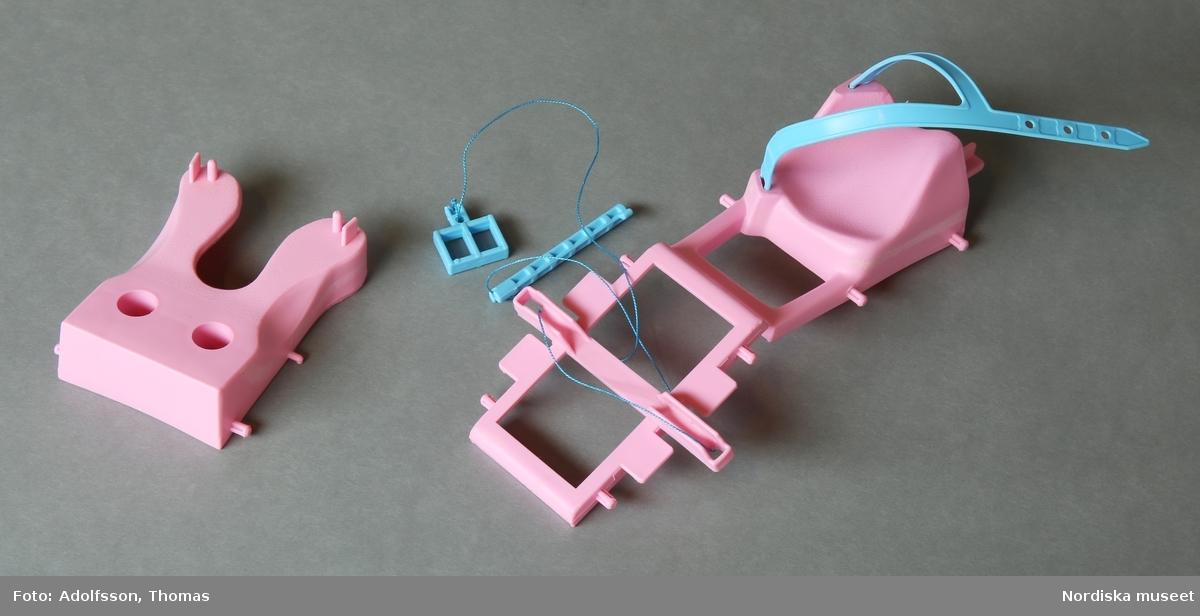 a:1-12) Byggsats med flera olika delar för dockgym till Barbiedocka. Delarna är av rosa och ljusblå plast och går att bygga ihop till träningsredskap av olika slag, varav b) en träningscykel är färdigmonterad. Till byggsatsen hör också c) ett skåp för träningskläder, samt d:1-2) två hantlar. Till byggsatsen hör också e:1-8) åtta lösa dekaler. f) Tillhörande kartong med bilder av hur dockan Barbie använder hantlar och andra redskap för styrketräning. Text på fyra olika språk: engelska, franska, tyska och italienska.