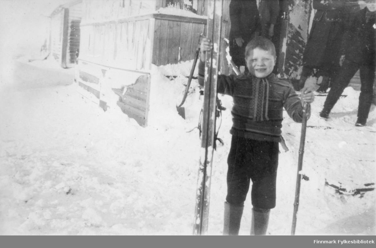 En gutt holder ski i hånden. Mye snø på bakken/veien. Noen personer står i bakgrunn ved døråpningen til huset.