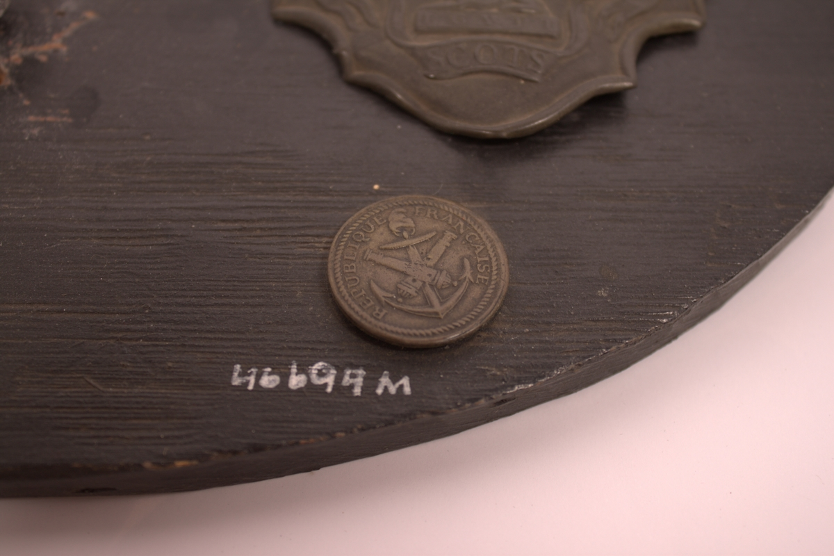 Uniformsknapp i messing 29.7mm stor. Beskrivelse se foto. På baksiden påloddet et øre som er delvis brukket. Knappen er sammen med andre gjenstander som er funnet på slagmarken ved Waerlo, montert på en oval sortmalt trelate med påskrift i hvit maling: *Waterlo 1815* 18/6.
