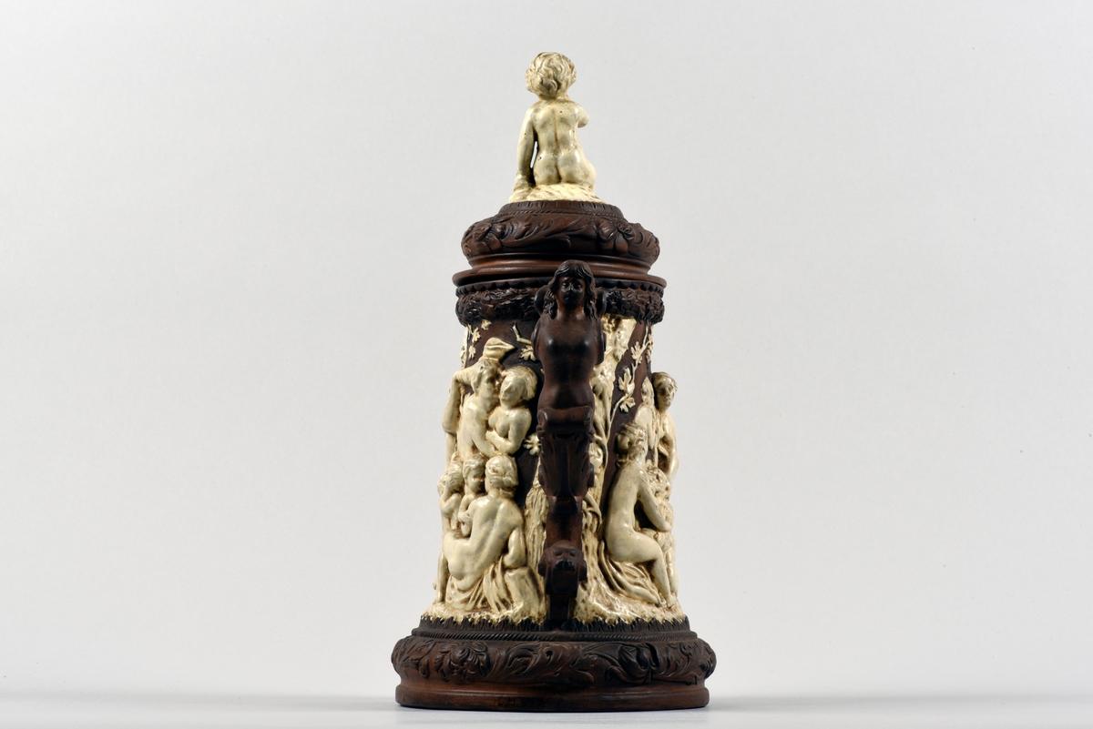 Brun dryckeskanna med öra och lock tillverkad i lergods. Stopet är rikt dekorerad i vitt med en backanalisk scen med ett myller av människor och djur bland vindruvsträd. Örat är utformat som en barbröstad ängel. På locket sitter en putti.