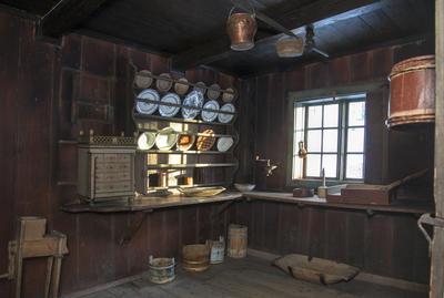 Interiør fra kjøkkenet i Skøienbygningen som viser en fullsatt tallerkenhylle i fire høyder og lyset som faller inn på porselenet gjennom et smårutete vindu.
