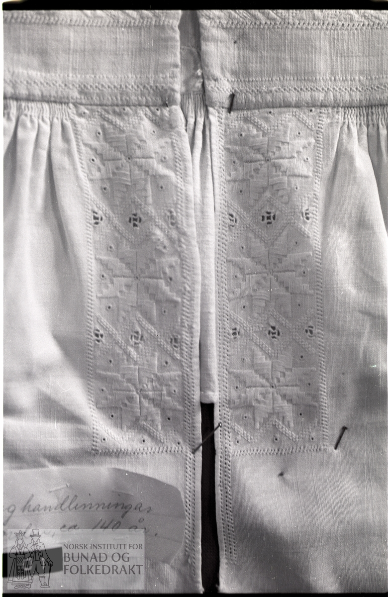 Nordhordlandsmessa 1974 nr. 96.  -  To framstykker breidde 14,5 cm, lengde 24 cm.  Eit bakstykke lengde:  12 cm av tynt bomullslerret.  Tett rynka til halslinning med ein rynketråd.  Breidde halslinning:  4,5 cm, breidde bord langs splitt:  4,2 cm, lengde bord langs splitt:  15 cm.  Borda langs splitten er fôra med samme stoff som i bakstykket.