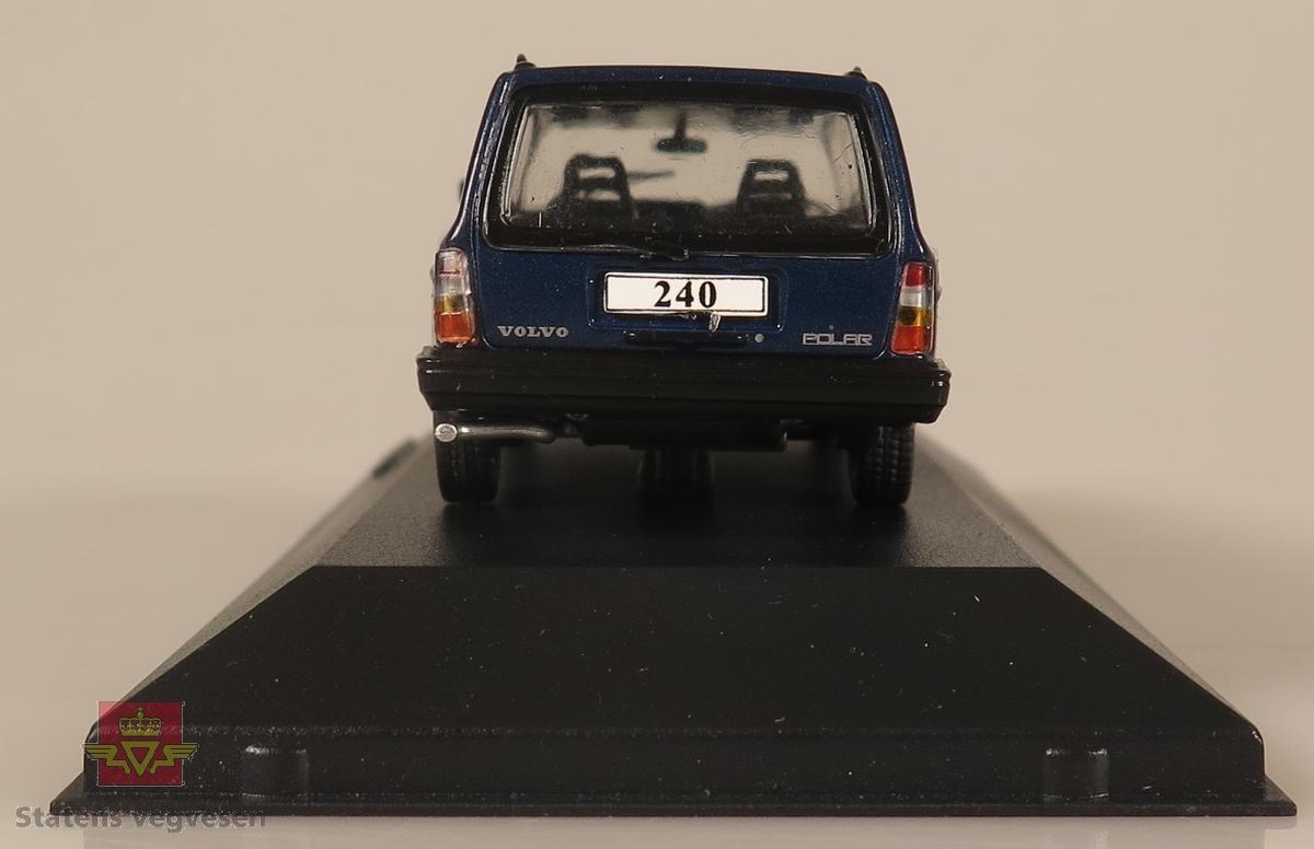 Primært blå plastbil som står festet på en svart plast sokkel. Innpakket i en blå pappeske.