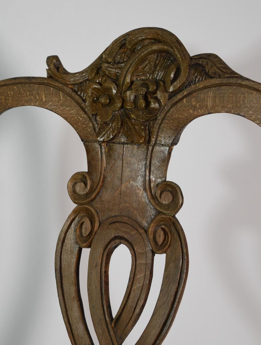 Stol av bøk, brunmalt med forgylling prydet med skårne dekorasjoner. Ryggen åpen sammensatt av loddrett midtfjel og en ramme i form av et langstrakt S-ledd på hver side. Midtfjelen er symmetrisk gjennombrutt og dannet av to åttetall flettet inn i hverandre. Fjelens topp er skjev, dannet av et smalt bladornament og derunder en plastisk skåren gren med to roser og tre blad. Setet er hesteskoformet. Sargen er vertikal, og fronten er prydet med et skjellornament hvis underkant går ned i en bue og kantes av et plastisk bladornament. Forbenene er S-formede, på den brede topp prydet med tre vifteformede ordnede bindingsbrett sammensatt av svungne ledd. Stoppet fast sete trukket med skinn.