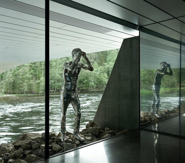 Speilblank mannsfigur står og lener seg mot utsiden av vinduet  under galleriene i The Twist. Han står med ruggen til elven og titter inn på alle som kommer ned trappen for å gå på toalettene.