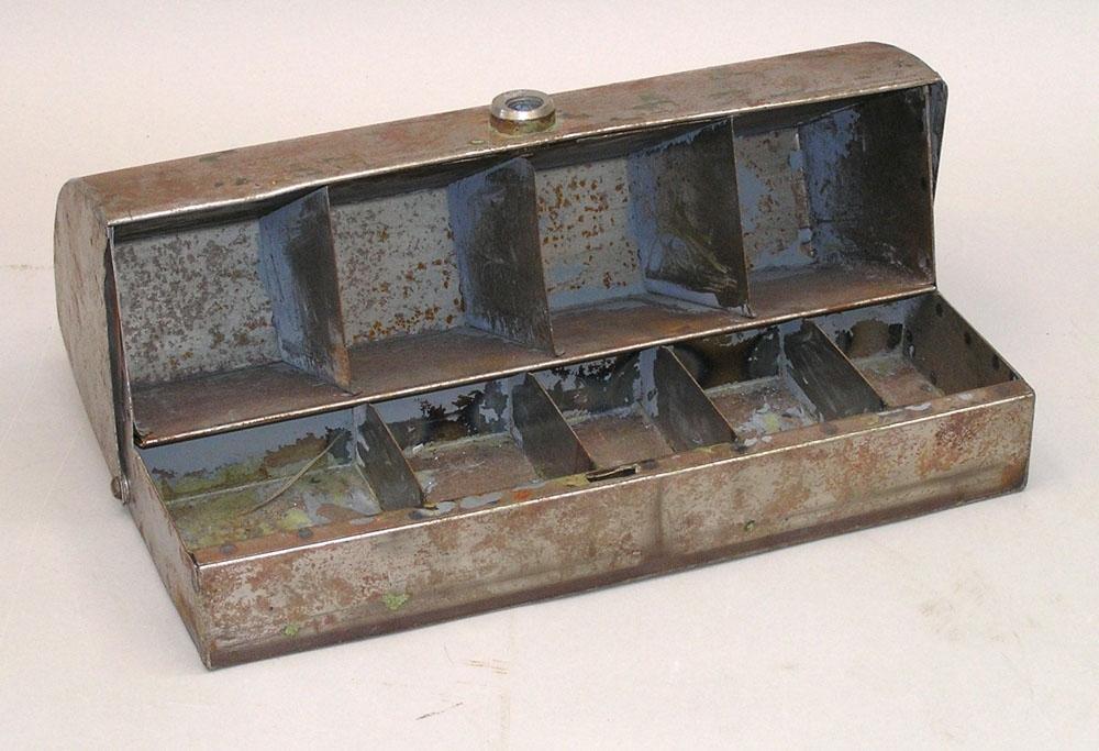 Kassaskrin av silverfärgad plåt med välvd lock. Skrinet har troligen varit grönmålat, men det mesta av färgen är borttagen eller bortnött. Låscylinder saknas.