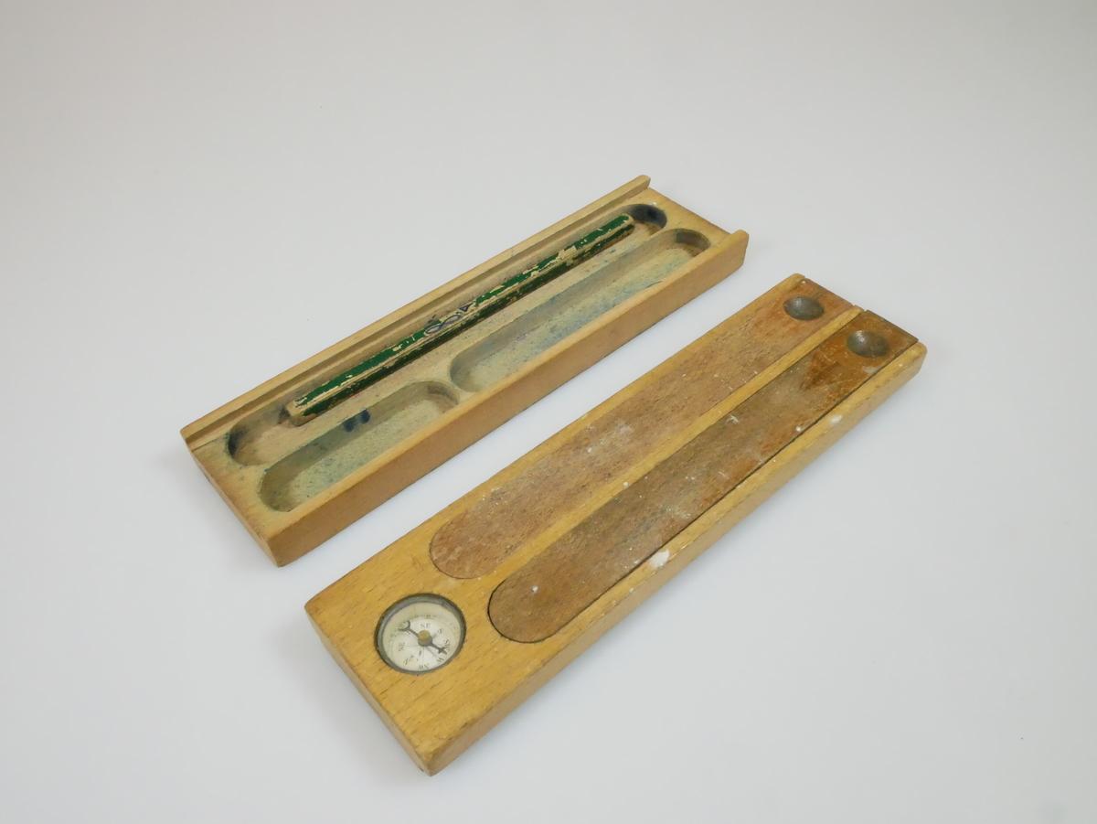 Rektangulært penal av brunt tre. Lokk med innebygd kompass og to trelengder som kan tas av, under er det rom for oppbevaring av skriveutstyr. I det ene rommet er det et rosa penneskaft med en penneslitt. Hele lokket kan tas av. Under er det tre rom, et med en grønn blyant i.