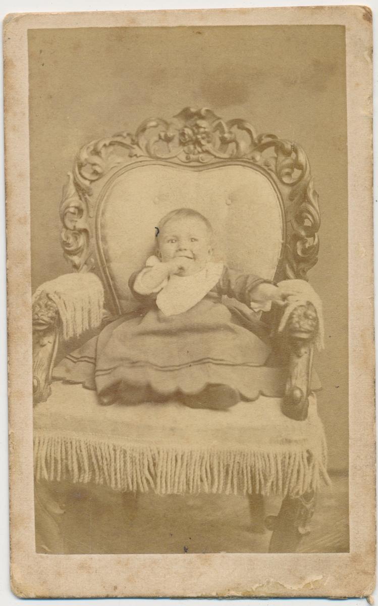 Lite barn sittende i stol, ukjent