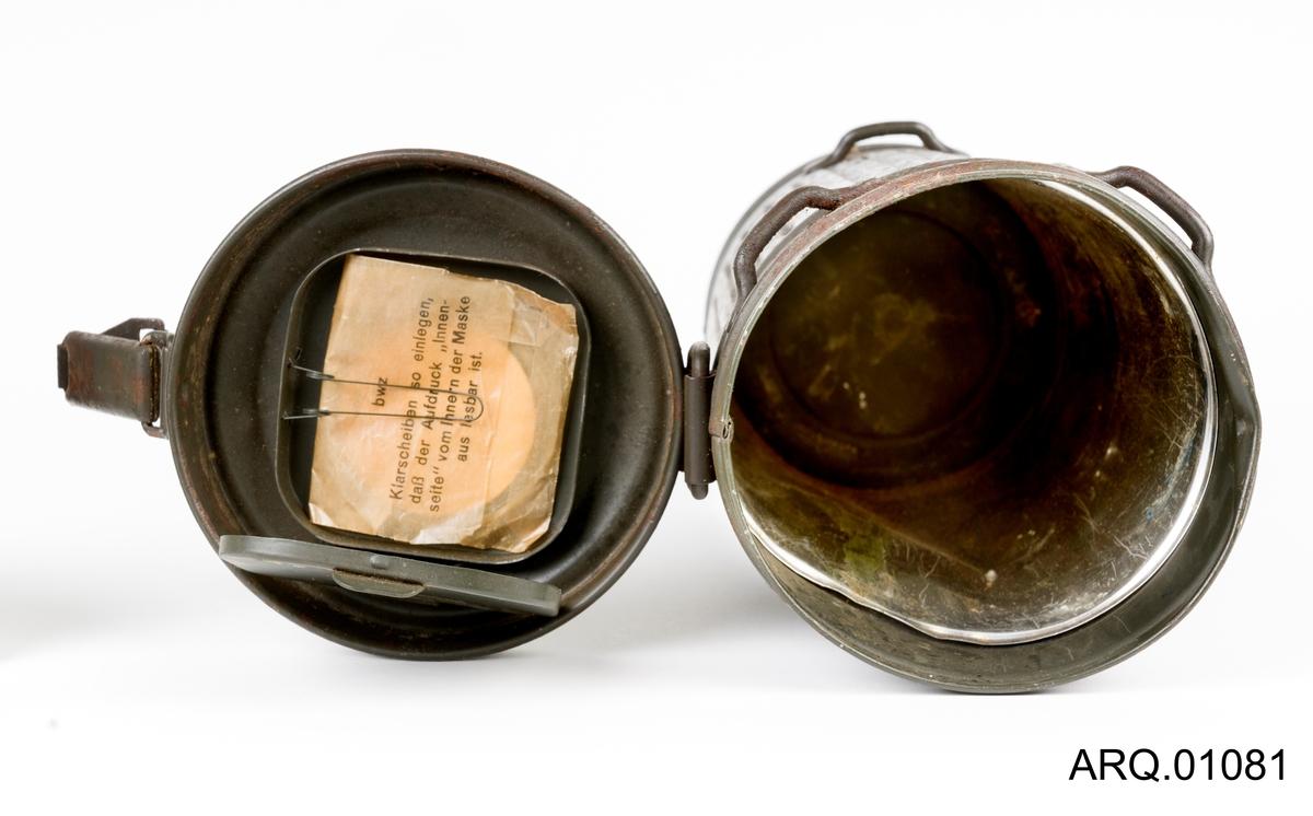 """Sylinderformet metallbeholder med hengslelokk og håndtak. Lokket har fjærbelastet lukkeordning. Riflete mønster rundt beholderen. Inne i beholderens lokk er det festet en liten boks hvor det er ekstrautstyr til gassmaske; """"glass"""" til gassmaskens øyne. Inne i denne lille esken ligger det noen slike glass, pakket i silkepapir, det står skrevet en bruksanvisning på papiret."""