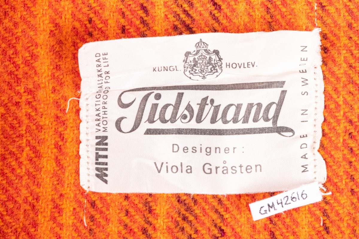 Orangerandig vävd yllefilt med fransar.
