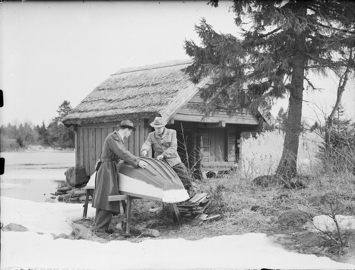 Två män vid eka, Östhammar, Uppland