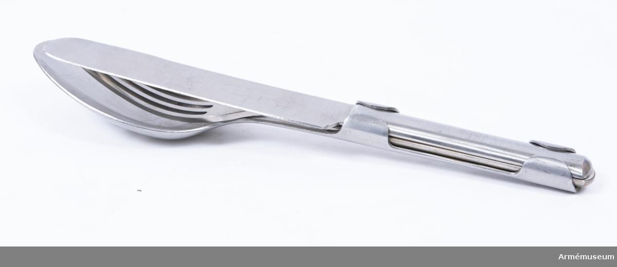 Matsked av rostfritt stål. På skedens handtag finns två breda, runda kalvringar för att sätta ihop matbesticket. Ingår i matbestick för menig vid armén, Finland, 1939.  Handtaget för gaffel  och sked halvrunt, för kniv flat.