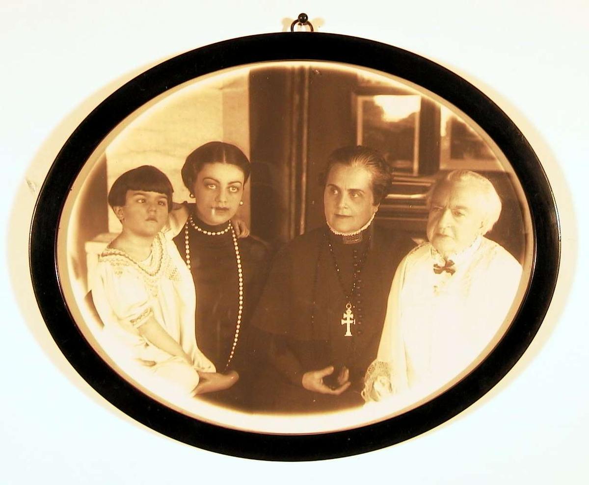 Familiefotografi, kvinneportrett i 4 generasjoner: oldemor i hvitt, mormor i sort, mor i sort, barn-datter i hvitt; alle sittende i halvkrets ved siden av hverandre. Ingen øyekontakt imellom dem eller betrakteren.