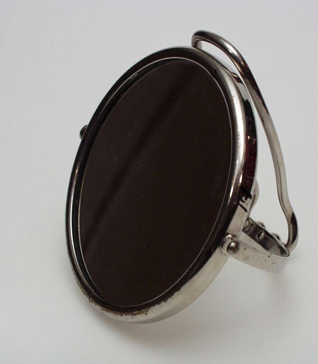 Rundt speil med dreibart skaft i metall som kan foldes sammen. Innramming i metall.  Den ene siden har et vanlig speil, den andre forstørrer.