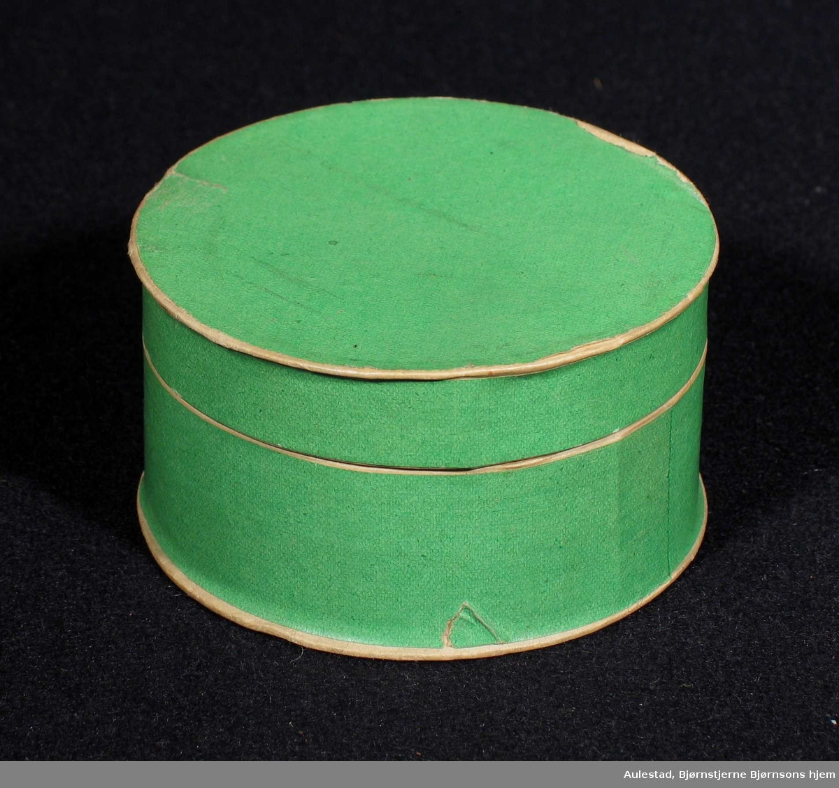 Rund grønn eske med lokk laget i kartong.