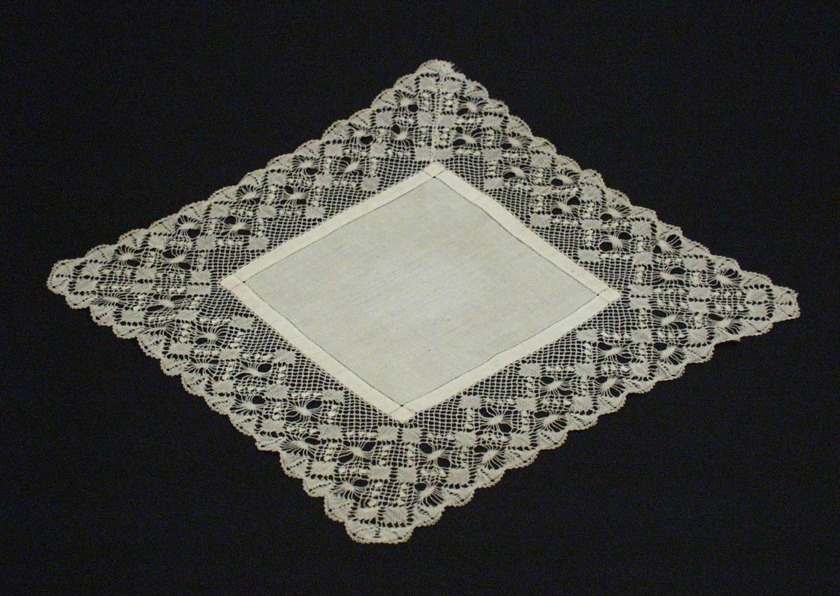 Hvit kniplet brikke i lin og bomull. Midtpartiet er 15x15 cm, av linlerret ca 44tr/cm er sydd med smal hullfald 9 mm inn fra brettekant. Kniplingskant 6 cm bred er kniplet som ramme med åpning 15x15 cm og sammensydd i et hjørne, diagonalt.