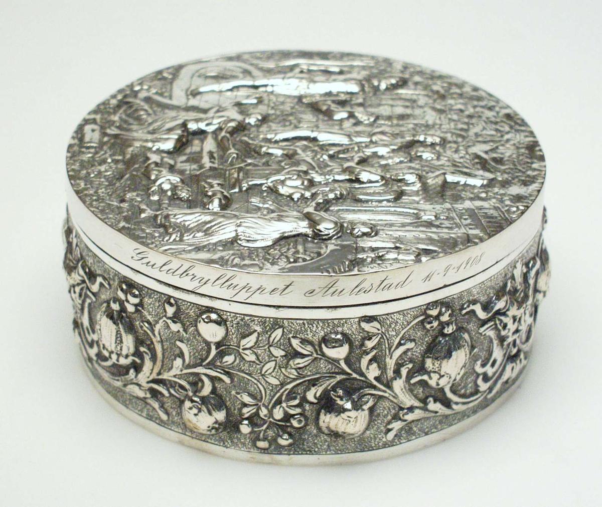 Rundt skrin i sølv med støpt dekor i relieff. På lokket et bibelsk motiv i relieff, på esken et rosemønster