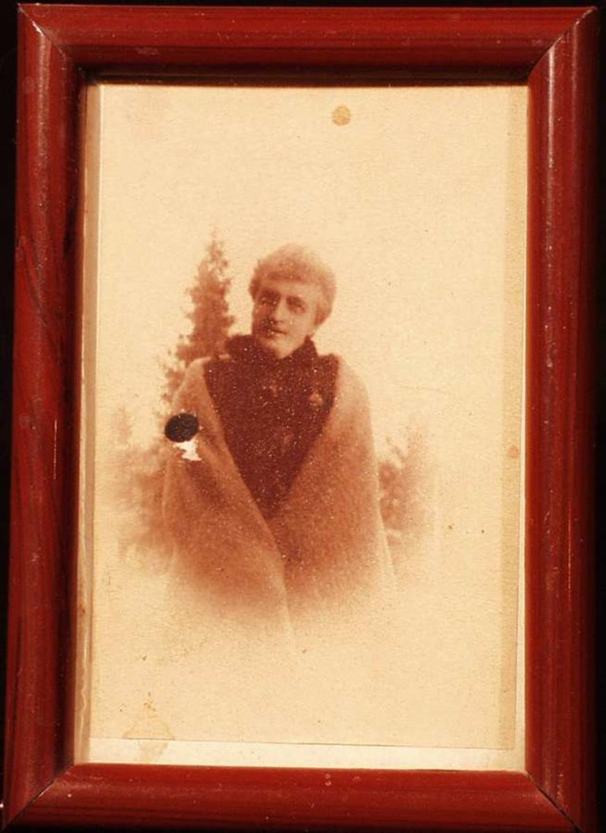 Karoline Bjørnson i sjal ved grantre.