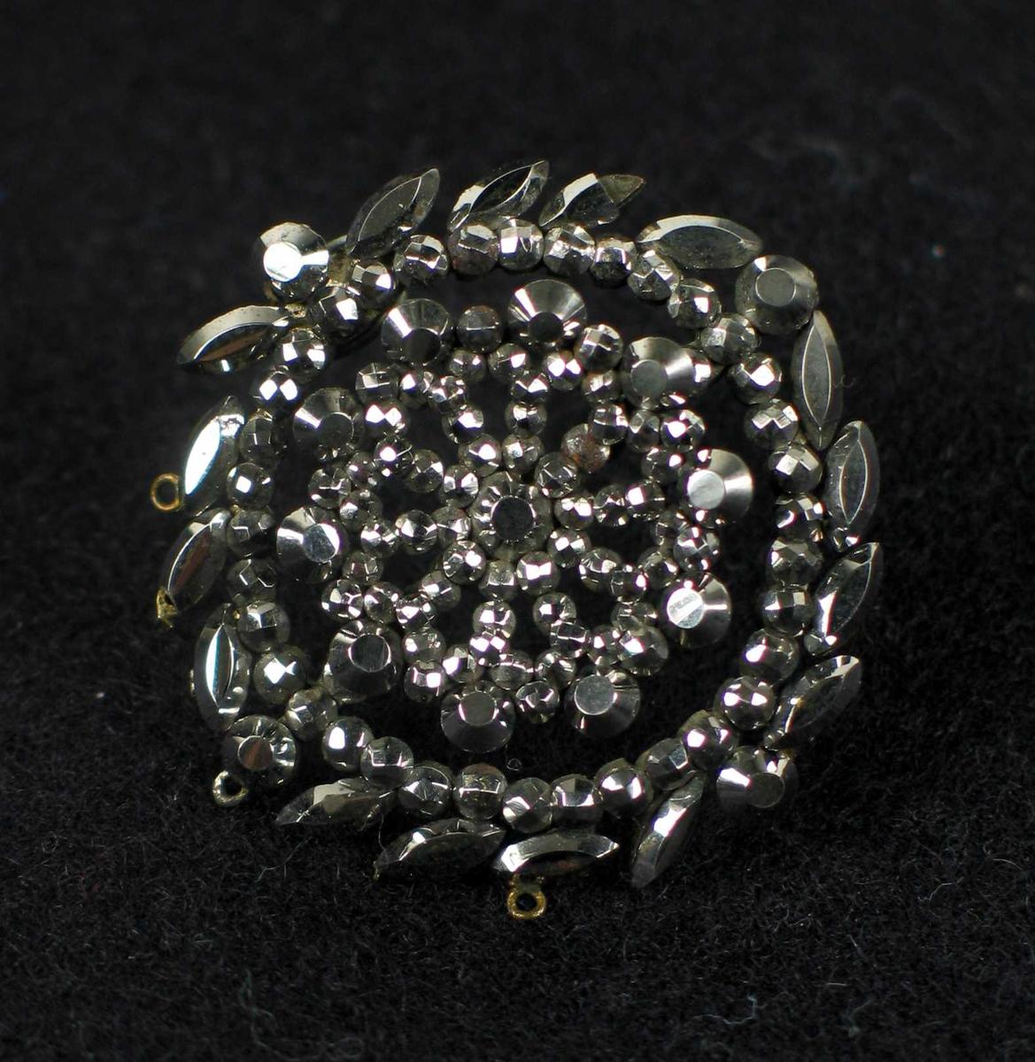Rund rosettformet nål i metall.
