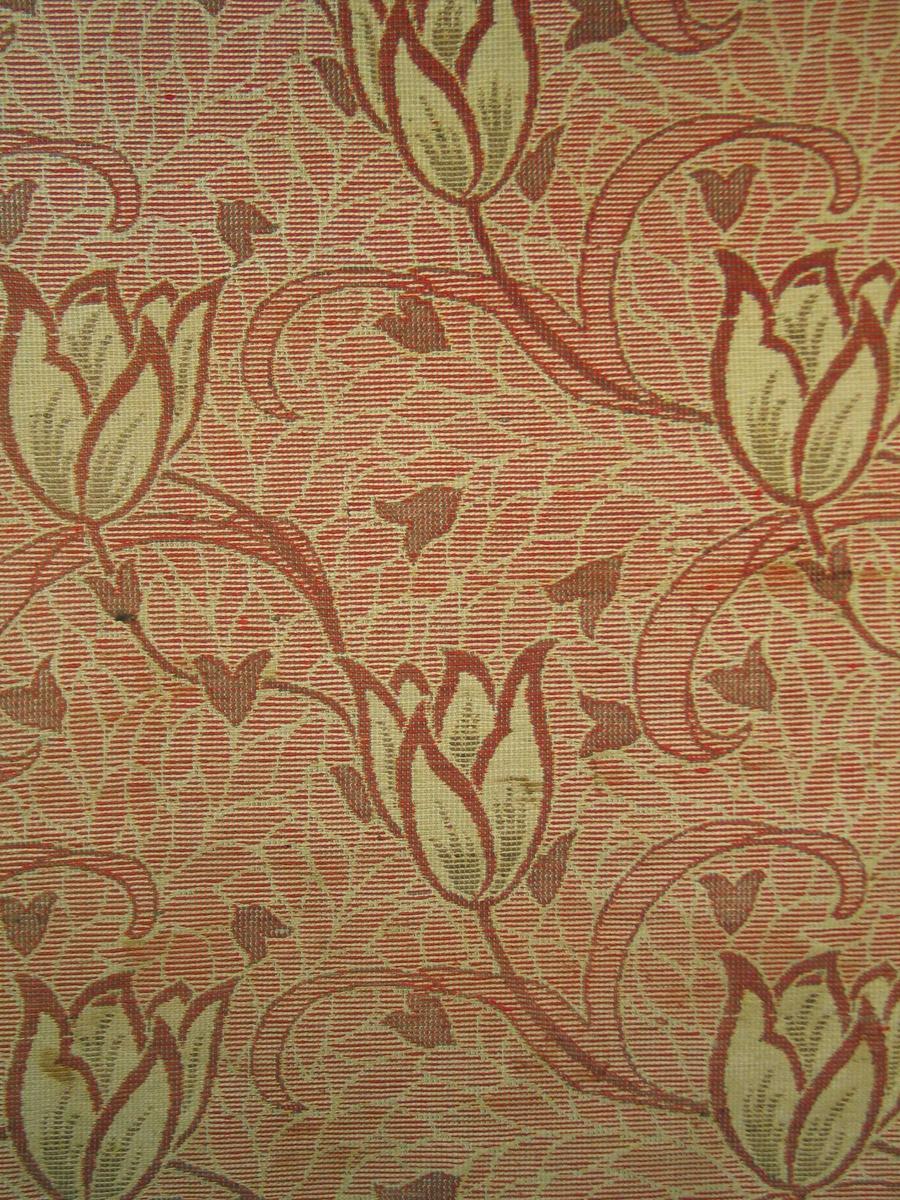 Golvtepperest. Stort luftig tulipanmotiv på en svakt beigekonturert rød bunn. Svungne linjer i blomst, stilk og blad.(Organisk)