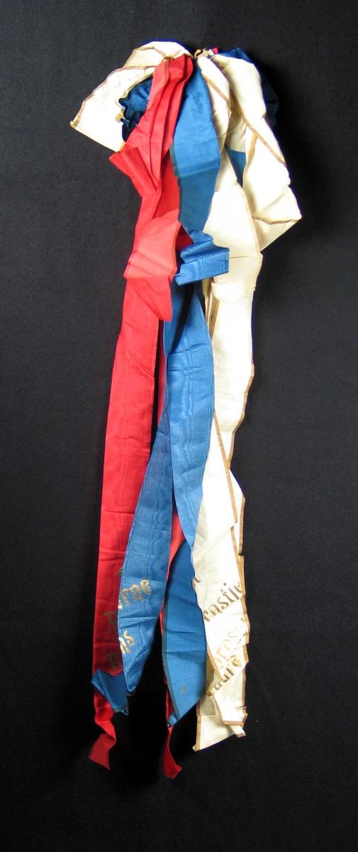 Begravelsessløyfe i rødt, hvitt og blått. Båndene har vært limt sammen.