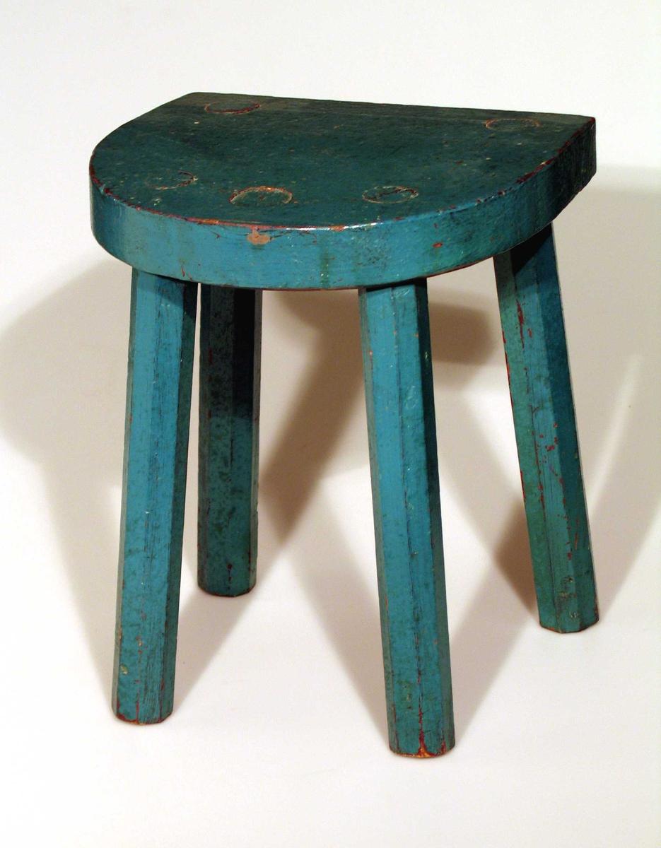 Peiskrakk med fire bein malt blågrønn. Setet er halvsirkelformet. Benene er åttekantet.