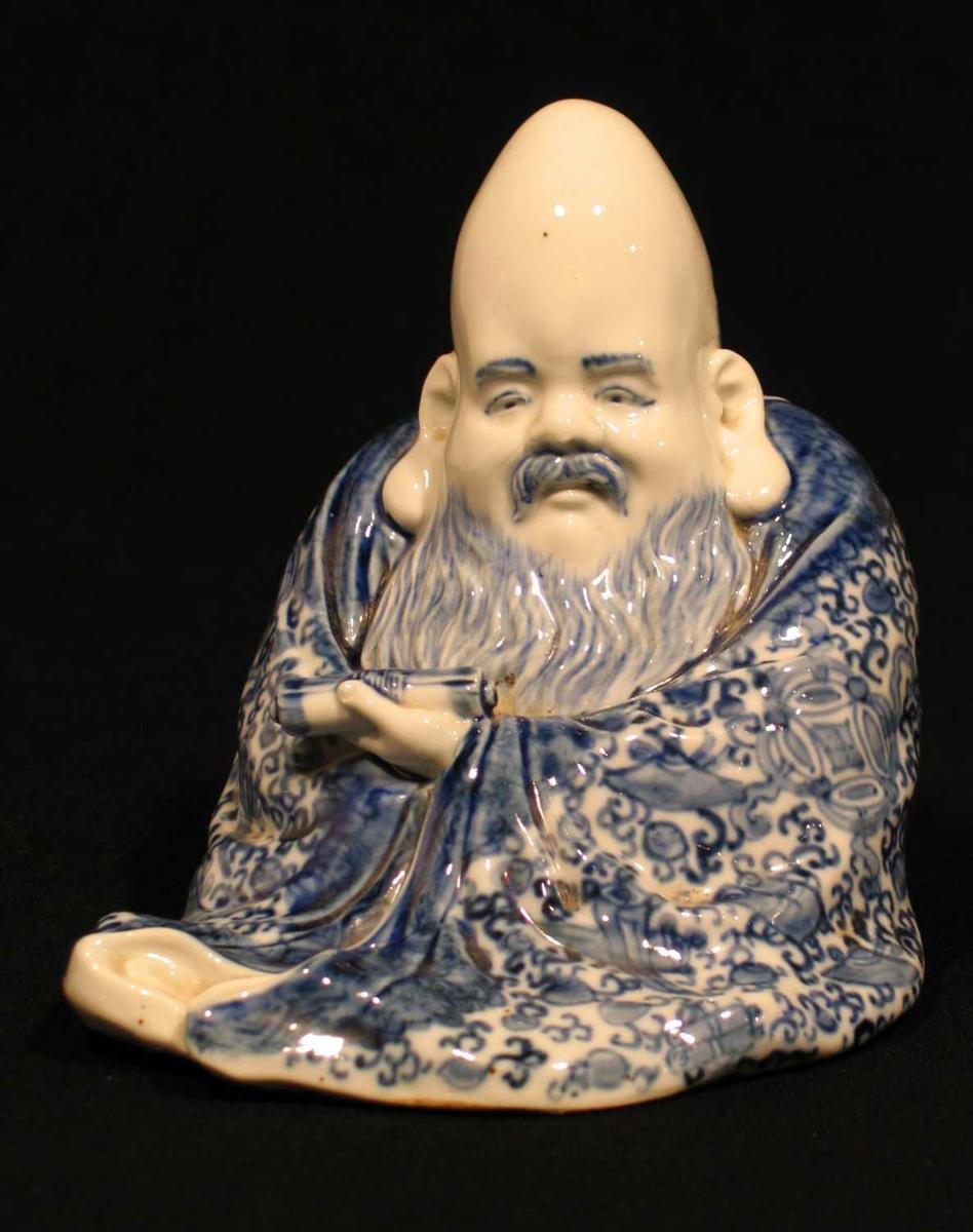 Japansk lykkegud i porselen. Sittende mann med brevrulle.