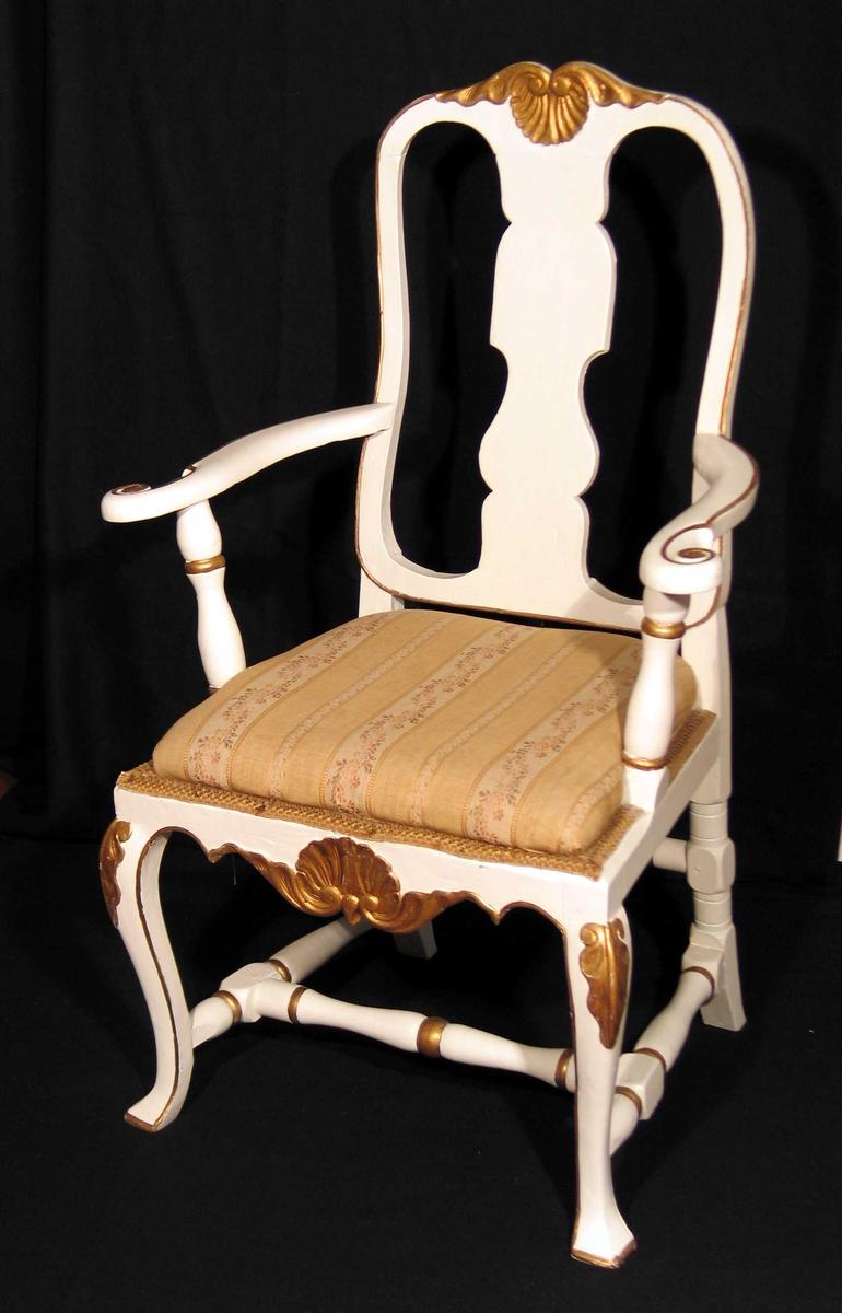 Hvitmalt armstol i bjørk med utskåret muslingmønster på toppstykke og sarg. Også utskåret ryggbrett og sprosser. Svungne forben og armlener. Bronsemalte detaljer. Setet er trukket om i brokadestoff (skaffet av Dagny.)