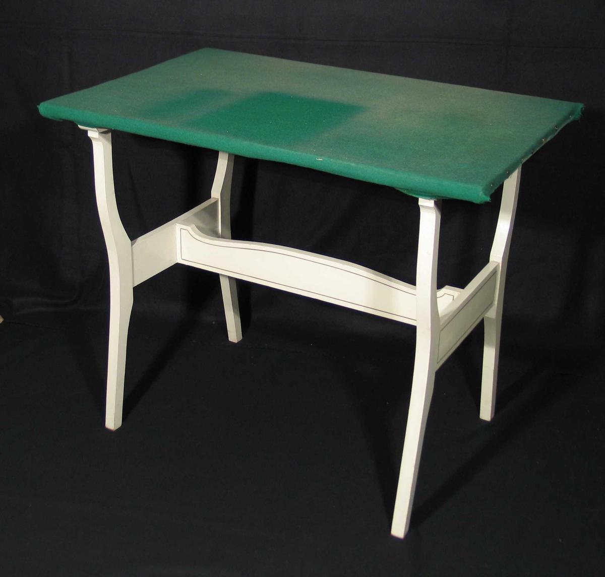 Hvitmalt bord med buede bein, tverrsprosse og strekkfisk. Platen er trukket med grønt ullstoff.