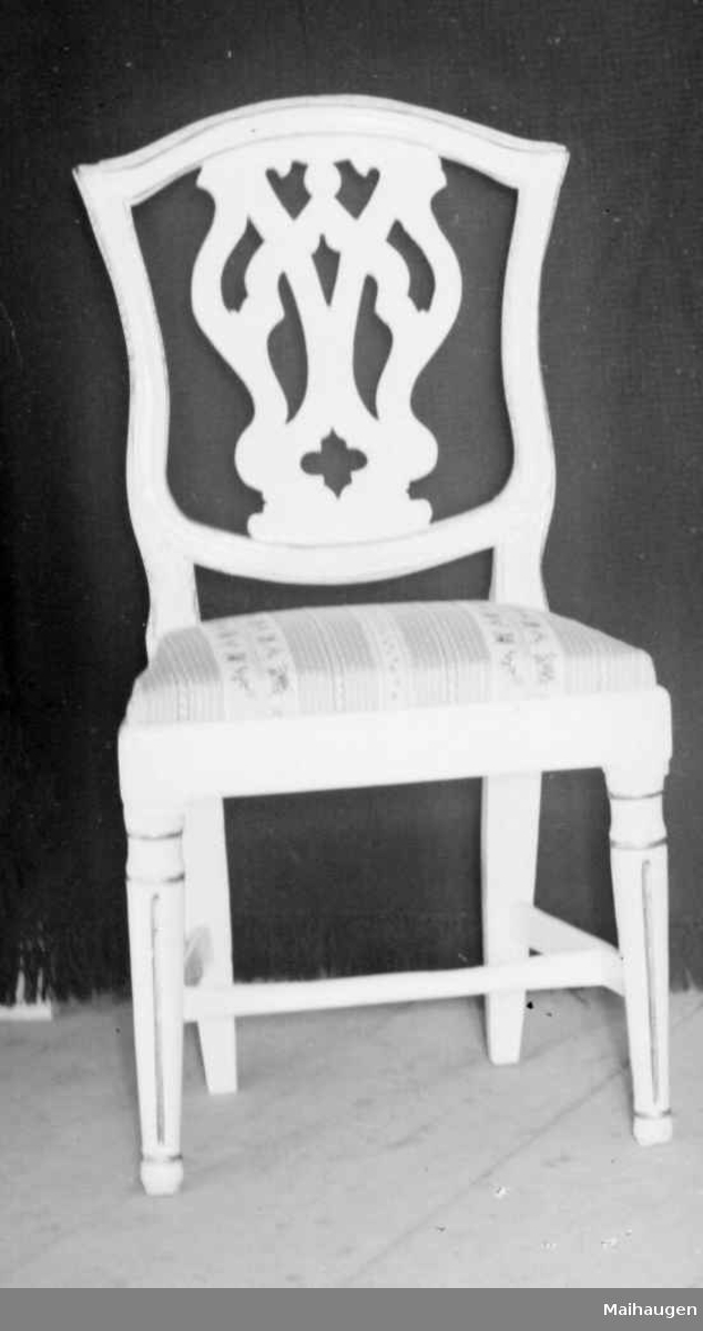 Stolen er i bjørk og gran, er hvitmalt med dekor i gull. Ryggbrettet er gjennombrutt og forbeina er runde, dreide og kannelerte. Stolen har løst sete som er stoppet med tekstiltrekk.