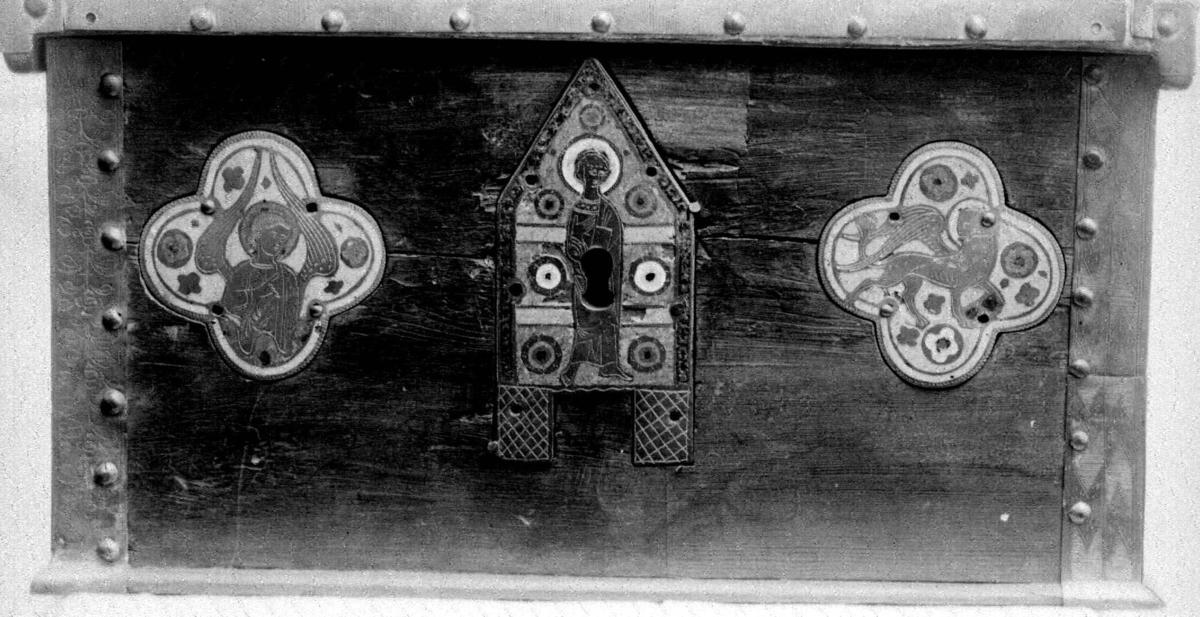 Skrin av tre med flatt lokk. På lokkets kanter og på skrinets hjørner er det beslag av messing. På lokkets beslag er det gravert en akantusranke på toppen og rutemønster, diapermotiver på sidene, mens det på hjørnebeslagene er chevronmotiver. På skrinets sider og på lokket er det innfelt messingbeslag med emaljedekor, limogerarbeider, alle med lys eller mørk blå emalje bakgrunn. Lokket har et beslag med bølgende kant der motivet er Kristus. Dette har trolig vært sentralbeslag på baksiden av et prosesjonskrusifiks. Framsida har to firpassbeslag med henholdsvis et bevinget menneske og en bevinget løve, evangelistsymbolene for Matteus og Markus. Disse er endebeslag fra korsarmene på et prosesjonskrusifiks eller alterkrusifiks.  I midten er det et gavlformet beslag med en stående helgenfigur. Dette er gavlen fra et lite relikvieskrin. Det er gjennomhullet med nøkkelhullformet hull. På høyre side av skrinet er det en framstilling av en talende Kristus i halvfigur på et rundt beslag og en framstilling av et bevinget menneske, evangelistsymbol for Matteus, fra et endebeslag fra et krusifiks. Baksiden av skrinet har i midten den andre gavlen fra et relikvieskrin, også her med en stående mannlig helgen uten attributter. På hver side av dette beslaget er det firpassformede beslag med ørn oge n bevinget okse, evangelistsymboler for Johannes og Lukas., begge har vært endebeslag på et krusifiks. På skrinets venstre side er det et rundt beslag med en halvfigur Kristusfigur som med talegest holder en rød boklignende gjenstand i sin venstre hånd. Under dette et oppned beslag med en ørn, evangelistsymbol for Johannes. Dette har også være endebeslag på toppet av et krusifiks.