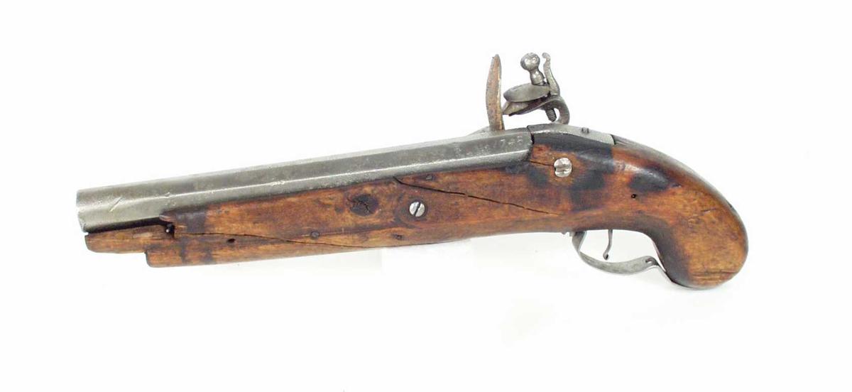 Sivil pistol med flintlås og løp fra gevær. Åttekantet glatt pipe. Pipen er stemplet : 1748 1731. Hvelvet låsblikk avrundet i forkant og med spiss bakkant.  Låsen festet med to gjennomgående skruer. Trekolbe.  Underbeslag i jern.